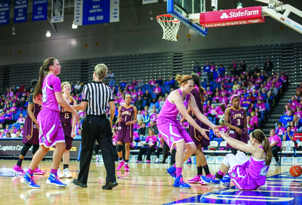 EMMA DONAHUE, Drake's lone senior, helps Caitlin Ingle off of the Knapp Center floor during the annual Pink Game on Feb. 26, the first of four Bulldog wins to finish the regular season. PHOTO BY MOHAMAD SUHAIMI | STAFF PHOTOGRAPHER